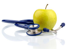 Apple and stethoscope. An apple and a stethoscope on a doctor. symbolic photo for healthy and vitamin-rich diet Stock Photo