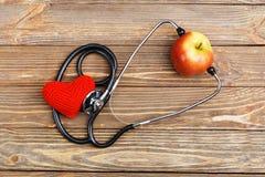 Apple, stetoskop i serce na drewnianym tle, Fotografia Royalty Free