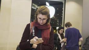 Apple Store Barcelona met vrouw die iPhone XS gebruiken stock video