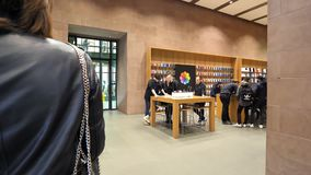 Apple Store computers shopping experience with customers being helped by genius
