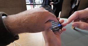 Apple Store con el hombre mayor compara el iPhone Xs y mapas almacen de metraje de vídeo