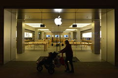Apple Store Exterior. BATH, UK - OCTOBER 20, 2015: A silhouetted woman pushes a pushchair past the exterior of a city centre Apple store. The American Stock Image