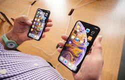 Apple Store with senior man comapre iPhone Xs and Xs Max. STRASBOURG, FRANCE - SEP 21, 2018: Apple Store with senior man customer POV comparing the new latest stock photography