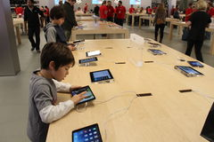 Apple Store. Two kids are trying  Apples new products ipad mini and iphone5 at Store in Bellevue Mall Square Royalty Free Stock Images