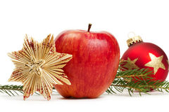 Apple straw star red christmas bauble and a branch. Red apple, a straw star and a red christmas bauble in background with a branch on white background Royalty Free Stock Images