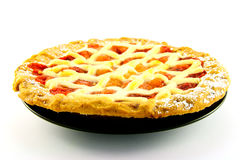 Apple and Strawberry Pie. Whole apple and strawberry pie on a black plate on a white background Royalty Free Stock Images