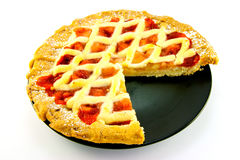 Apple and Strawberry Pie with a Slice Missing. Whole apple and strawberry pie on a black plate with a slice missing on a white background Royalty Free Stock Image