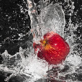 Apple in streaming splash water on black Royalty Free Stock Image
