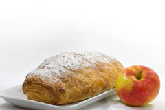 Apple strudel with apple. An apple is located on the side of apple strudel Royalty Free Stock Image