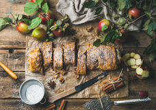 Apple strudel cake with cinnamon, nuts and sugar powder. Apple strudel cake with cinnamon and sugar powder cut in slices served with star anise, nuts and fresh Stock Photography