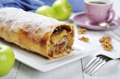 Apple strudel. On a dish with fresh apples and cup of coffee Royalty Free Stock Image