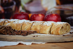 Apple strudel with fresh apples, anason and cinnamon on a wooden board. Closeup Stock Image