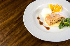 Apple strudel with ice cream and orange on white plate Royalty Free Stock Photos