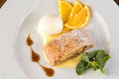 Apple strudel with ice cream and orange on white plate Royalty Free Stock Images
