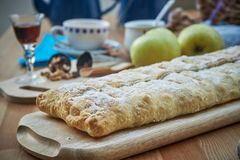 Apple strudel with nuts, raisins, cinnamon and powdered sugar. Homemade apple strudel with fresh apples. Country style apple. Strudel royalty free stock photography