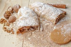 Apple strudel with nuts, raisins, cinnamon and powdered sugar. royalty free stock photography