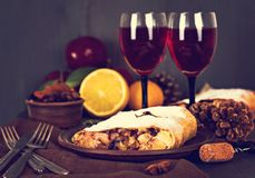 Strudel and wine. Apple strudel (pie) with dried fruits, oranges, cranberries, walnuts with sugar and  red wine on dark background.   Lunch, dinner for two Royalty Free Stock Images