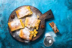 Apple strudel pie. Puff pastry cutting on the board. Traditional  Austrian Viennese strudel with apple spices and sugar powder. Top view copy space Royalty Free Stock Images