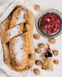 Apple strudel with raspberries on wooden board. Homemade Apple strudel with raspberries on wooden board served with walnuts, white background, top view Royalty Free Stock Image