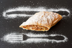 Apple strudel on a slate board with the design of icing sugar Stock Photography
