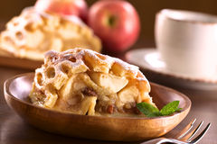 Apple Strudel. Slice of fresh apple strudel with raisins on rustic wooden plate with coffee cup in back (Selective Focus, Focus on the left side of the apple Stock Image