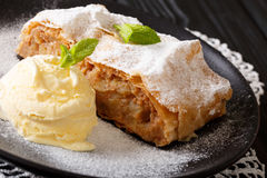 Apple strudel sprinkled with powdered sugar with ice cream and m. Int closeup on a plate. horizontal stock photos