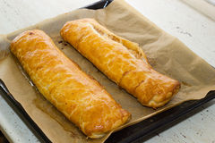 Apple strudel. Two homemade freshly baked apple strudel on baking paper Royalty Free Stock Photography