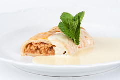 Apple strudel with vanilla cream. On white plate Royalty Free Stock Photos