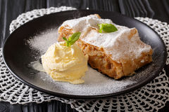 Apple strudel with vanilla ice cream close-up. Horizontal. Apple strudel with vanilla ice cream on a plate close-up. Horizontal Royalty Free Stock Photos