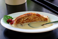 Apple strudel with vanilla sauce. On table Royalty Free Stock Photos