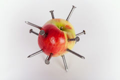 Apple stuck with iron nails Royalty Free Stock Photography