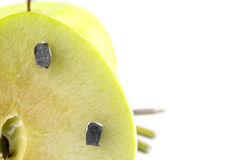 Apple stuck with nails, detail of a fruit with iron, tool Royalty Free Stock Image