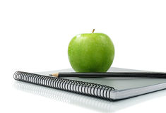 Apple Study II. Studio macro of shiny green apple, pencil and new notebook on a white surface. Copy space stock photo