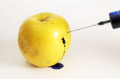 Apple stung by syringe with poison. Yellow apple stung by syringe with poison Royalty Free Stock Photos
