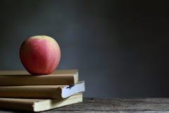 Apple sul libro e sul fondo nero Immagini Stock Libere da Diritti