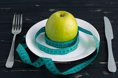 Apple sul piatto con nastro adesivo di misurazione sui precedenti di legno Fotografie Stock Libere da Diritti