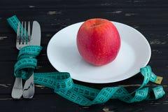 Apple sul piatto con nastro adesivo di misurazione sui precedenti di legno Fotografia Stock Libera da Diritti