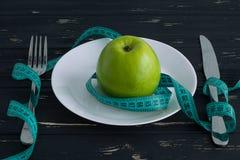 Apple sul piatto con nastro adesivo di misurazione sui precedenti di legno Immagini Stock Libere da Diritti
