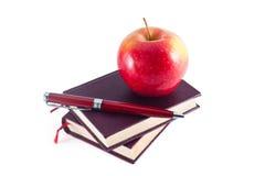 Apple sulla pila di libri con la penna Fotografia Stock