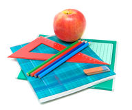 Apple and supplies on a white background. Red apple, notebooks, pencils, eraser and ruler on a white background Royalty Free Stock Photography