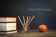 Apple sur des livres avec les crayons et le tableau noir vide - de nouveau à l'école image libre de droits