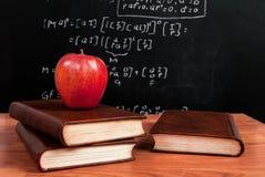 Apple sur des livres sur un bureau en bois pendant les maths classent dans la salle de classe Photos stock