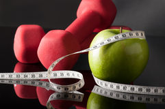 Apple and dumbells surrounded by tapeline Stock Photography