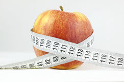 Apple surrounded by a measuring tape Health and fitness concept Stock Photo