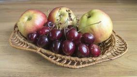 Apple and sweet cherries on table. Ripe apple and sweet cherries in braided plate on wooden table Stock Photo