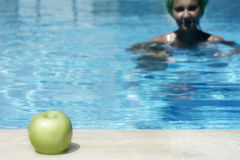 Apple after swim. Young lady swimming to an apple in the corner of the pool Royalty Free Stock Photos