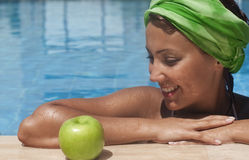 Apple after swim. Young woman at pool looking to an apple with appetite Stock Image