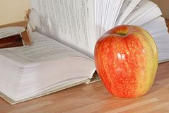 Apple on a table. With book and glasses royalty free stock photo