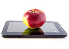 Apple on the tablet computer. Apple lies on a surface the screen of a touch tablet Stock Image