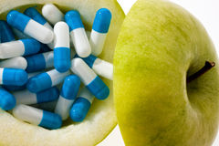Apple with tablets capsules. Royalty Free Stock Photo